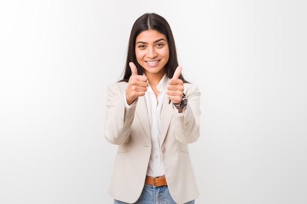 A mulher árabe do negócio novo isolada contra uma parede branca com polegares levanta, elogios sobre algo, apoia e respeita o conceito.