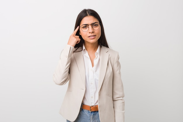 A mulher árabe do negócio novo isolou o branco que mostra um gesto da decepção com dedo indicador.