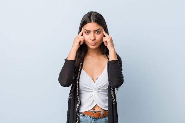 A mulher árabe natural e bonita nova focalizou em uma tarefa, mantendo os dedos indicadores que apontam a cabeça.