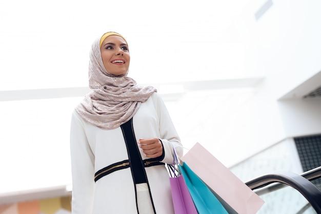 A mulher árabe nova está estando perto da escada rolante.