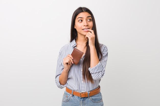 A mulher árabe nova que guarda uma carteira relaxou o pensamento sobre algo que olha um espaço em branco.