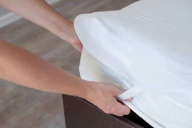 A mulher arruma a cama, colocando uma capa protetora à prova d'água sobre o colchão. roupa limpa e sono confortável.