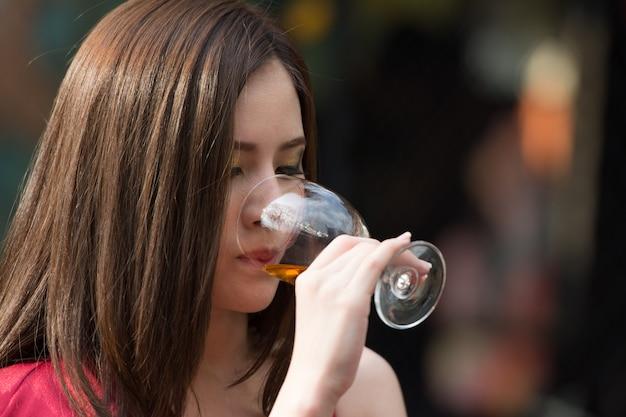 A mulher asiática bebe o vidro da bebida do álcool na barra da noite.