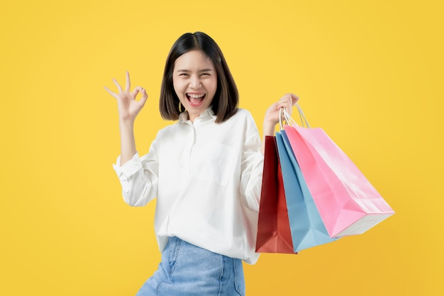 A mulher asiática bonita alegre que guarda multi sacos de compras e mostras coloridos assina o sinal aprovado.