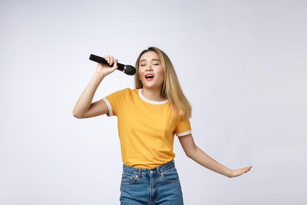 A mulher asiática bonita canta uma música ao microfone, estúdio do retrato no fundo branco.