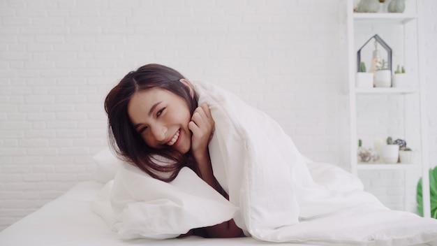 A mulher asiática bonita feliz acorda, sorrindo e esticando seus braços em sua cama no quarto.