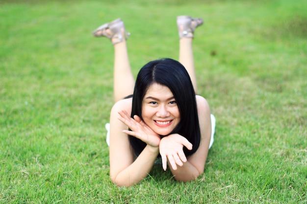 A mulher asiática bonita no vestido branco relaxa e sorrindo no campo verde no parque natural. jovem tailandesa desfrutar de férias com a luz solar no jardim