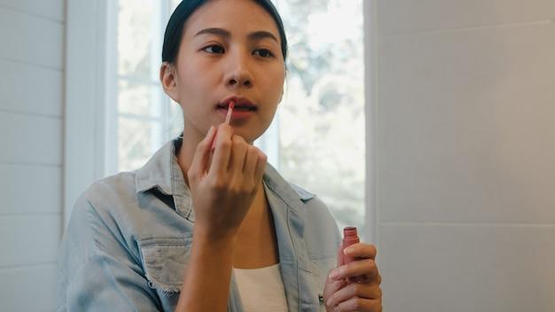 A mulher asiática bonita que usa o batom compõe no espelho dianteiro, fêmea chinesa feliz que usa cosméticos da beleza para melhorar-se pronta para trabalhar no banheiro em casa. estilo de vida as mulheres relaxam em casa
