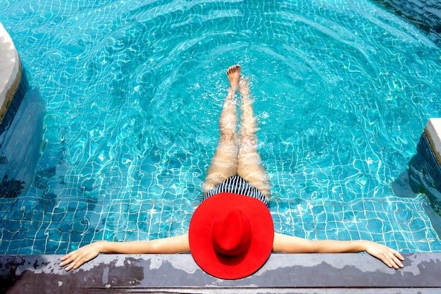 A mulher asiática com chapéu vermelho relaxa na piscina.
