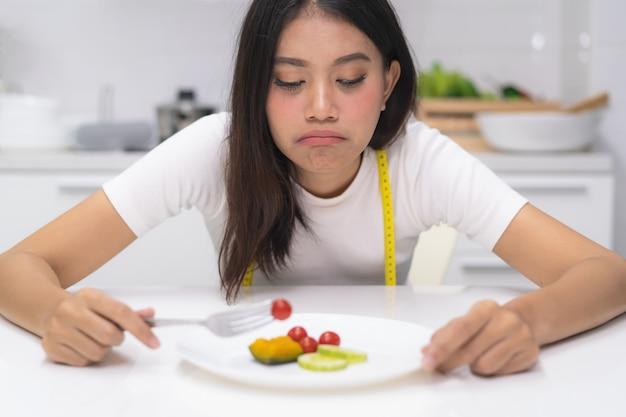 A mulher asiática come a desordem durante a dieta.