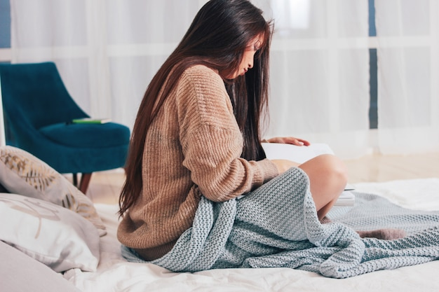 A mulher asiática da menina longa bonita do cabelo que senta-se na cama com livro, tempo home acolhedor