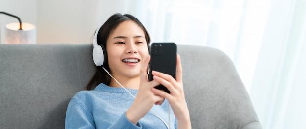 A mulher asiática de sorriso feliz ouvindo música dos fones de ouvido brancos e usando as mãos toca no smartphone de férias em casa.