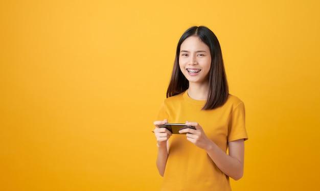 A mulher asiática de sorriso nova joga jogos no smartphone e vista no fundo amarelo.