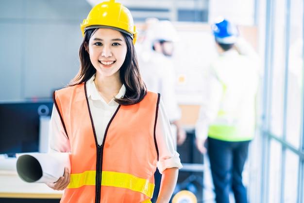 A mulher asiática do engenheiro do sorriso segura o desenho da planta, enquanto os membros da equipe dão alguns brainstorm para a idéia do controle da estrutura