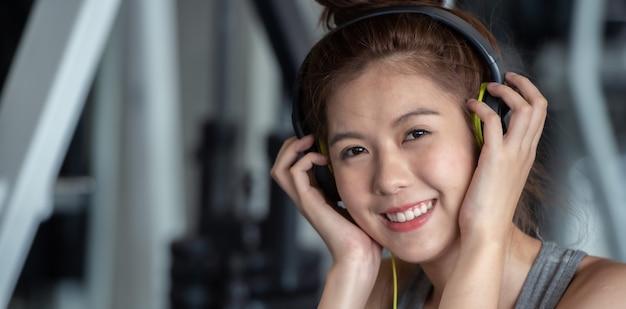 A mulher asiática do esporte com fones de ouvido que escuta a música relaxa após o exercício duro do exercício no gym do esporte.