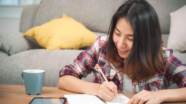 A mulher asiática do estudante faz trabalhos de casa em casa, tabuleta de utilização fêmea para procurarar no sofá na sala de visitas em casa. as mulheres do estilo de vida relaxam em casa o conceito.