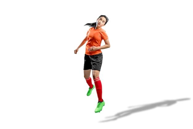 A mulher asiática do jogador de futebol salta no ar e tentando encabeçar a bola
