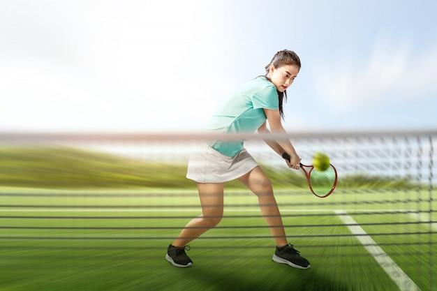 A mulher asiática do jogador de tênis com uma raquete de tênis em suas mãos bate a bola