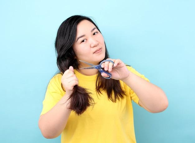 A mulher asiática do retrato quer cortar o cabelo danificado, sobre fundo azul no estúdio.