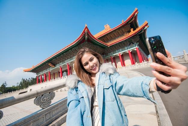 A mulher asiática do turista selfing com seu telefone esperto no marco de taipei