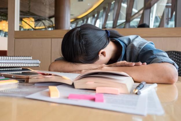 A mulher asiática dormiu sentada na mesa depois que ela tentou ler um livro em tempo de descanso na mesa de madeira borrada e fundo texturado na sala de reuniões, tempo feliz e relaxamento do conceito da mulher