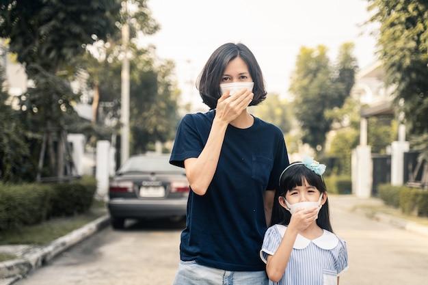 A mulher asiática e a filha nova pequena que vestem a máscara para impedem o crepúsculo pm 2.5 poluição de ar ruim fora da casa.