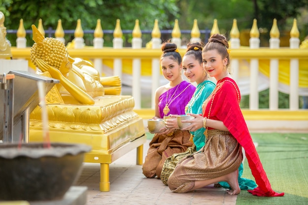 A mulher asiática está banhando a estátua da buda felizmente em tailândia.