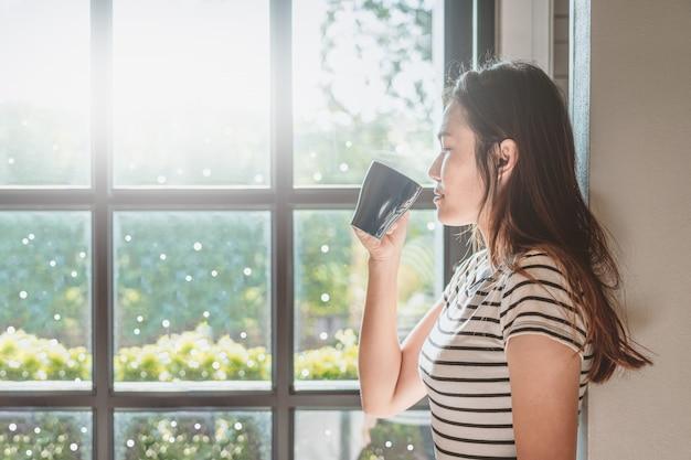 A mulher asiática está bebendo o café quente em sua casa.