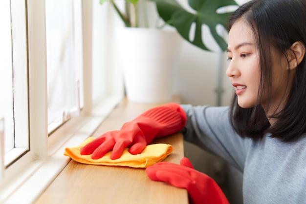 A mulher asiática está usando um pano que limpa para fora a poeira no contador de madeira.