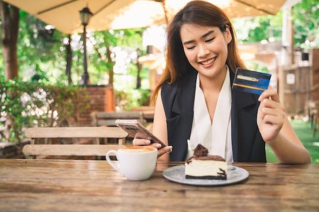 A mulher asiática feliz atrativa nova está usando a tabuleta ou o smartphone para fazer compras e pagar em linha pelo débito ou pelos cartões de crédito