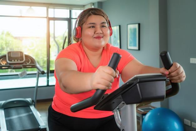 A mulher asiática feliz do excesso de peso com treinamento do fone de ouvido na bicicleta ergométrica no gym moderno, feliz e sorri durante o exercício.