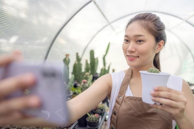 A mulher asiática gosta de cultivar cactos e é proprietária de uma empresa iniciante que vende árvores online.