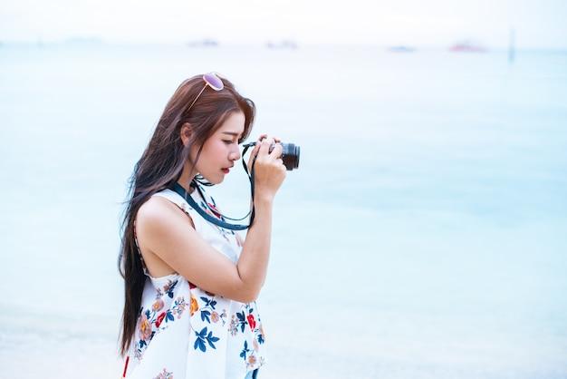 A mulher asiática gosta de tirar foto pela câmera digital na praia