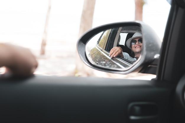 A mulher asiática na camisa branca está olhando no espelho da vista lateral e está sorrindo ao sentar-se em seu carro, conceito do curso.