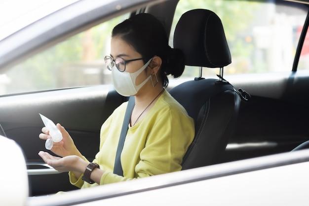 A mulher asiática na camisa verde ou amarela usa máscara protetora usando gel desinfetante para as mãos nas palmas das mãos para evitar o coronavírus ou o coronavírus antes de dirigir um carro.