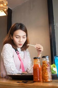 A mulher asiática nova aprecia comer o potenciômetro quente japonês de shabu-shabu