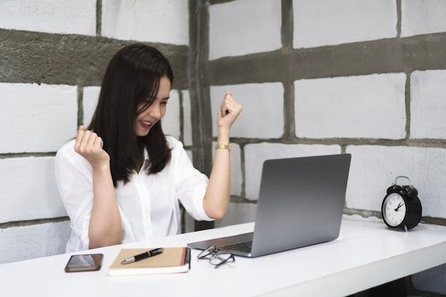 A mulher asiática nova bem sucedida feliz comemora ao trabalhar com portátil em casa.