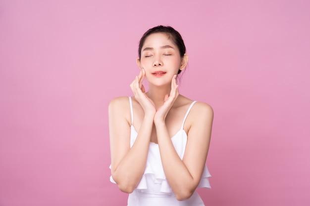 A mulher asiática nova bonita com a pele branca fresca limpa que toca na cara suavemente, pose da beleza, olhos fechados pôs as mãos no fundo isolado bochecha.