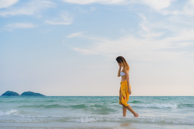 A mulher asiática nova bonita feliz relaxa andando na praia perto do mar.
