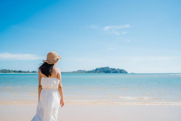 A mulher asiática nova bonita feliz relaxa o passeio na praia perto do mar.