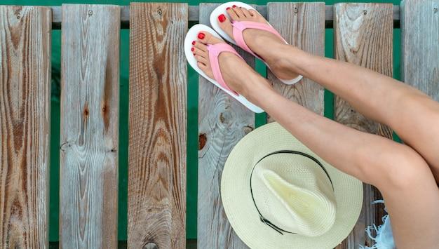 A mulher asiática nova com pedicure vermelho que veste sandálias cor-de-rosa e brancas senta-se na ponte de madeira e põe o chapéu ao lado das pernas no feriado. férias de verão. vibes do verão. mulher viaja sozinha.