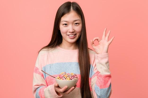 A mulher asiática nova com uma bacia de cereal alegre e segura mostrando o gesto aprovado.