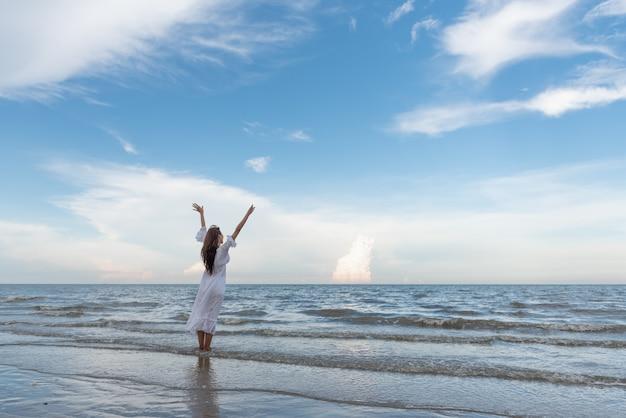 A mulher asiática nova de viagem levantou o braço na praia.