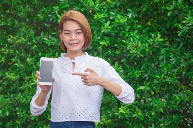 A mulher asiática nova do sorriso mostra o polegar acima com o smartphone nas folhas verdes.
