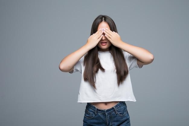 A mulher asiática nova esconde sua cara, foto do estúdio no fundo cinzento. conceito de problema de fobia social. menina cobre o rosto com as mãos, sentindo a emoção do medo.