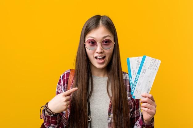 A mulher asiática nova que guarda passagens aéreas surpreendeu apontar a si mesmo, sorrindo amplamente.
