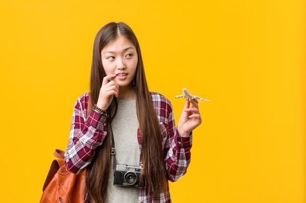 A mulher asiática nova que guarda um ícone do avião relaxou o pensamento sobre algo que olha um espaço da cópia.