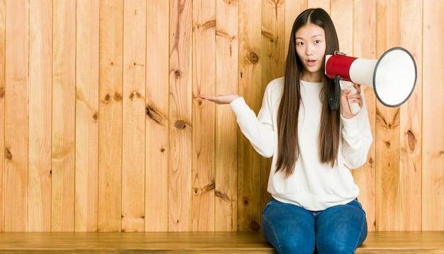 A mulher asiática nova que guarda um megafone imprimiu guardar o espaço da cópia na palma.