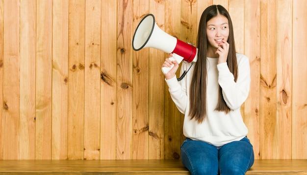 A mulher asiática nova que guarda um megafone relaxou o pensamento sobre algo que olha um espaço da cópia.