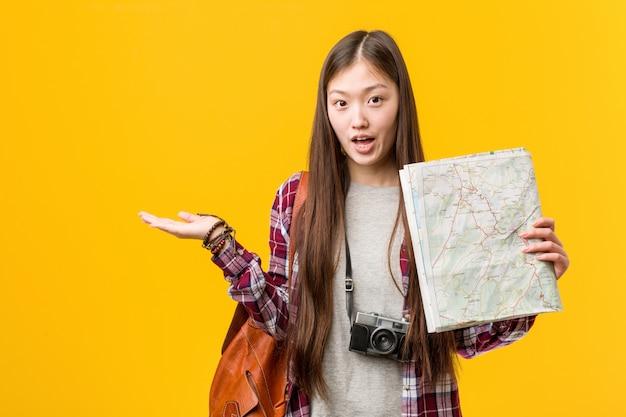 A mulher asiática nova que guardara um mapa imprimiu guardar o espaço da cópia na palma.